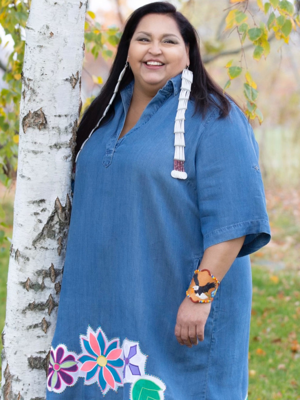 A person with long dark hair poses for a photo next to a tree in a blue dress with multi-colored floral patterns near the bottom