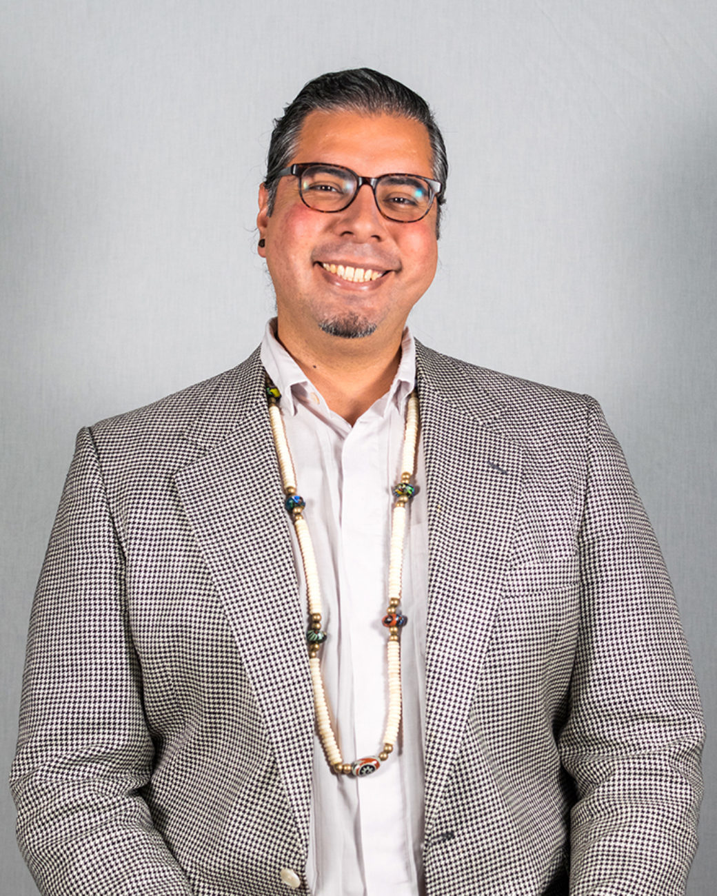 A person with dark hair and glasses poses for a photo, wearing a gray blazer and a beaded necklace