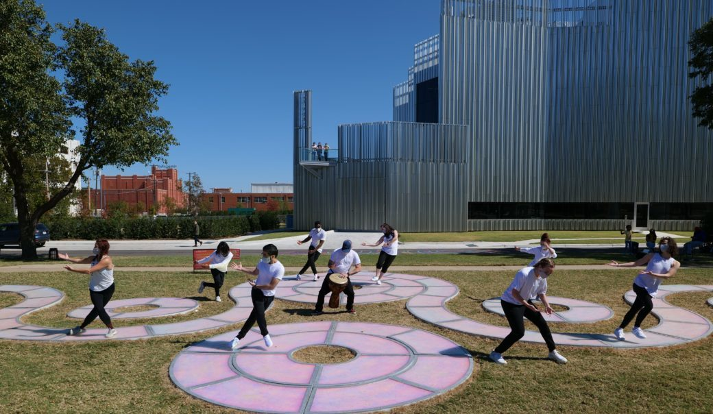 Dancers perform on a public art sculpture resembling winding, conjoined circles outside a metal building on a blue day
