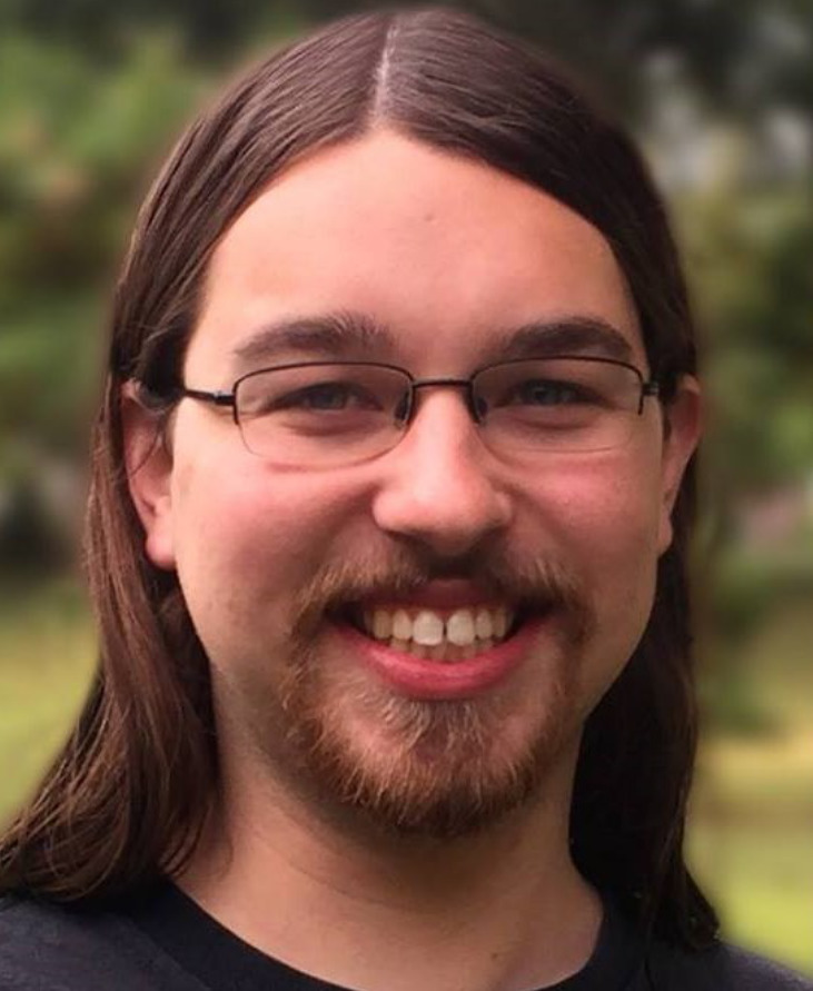 A headshot of a smiling person with glasses, long hair and a goatee