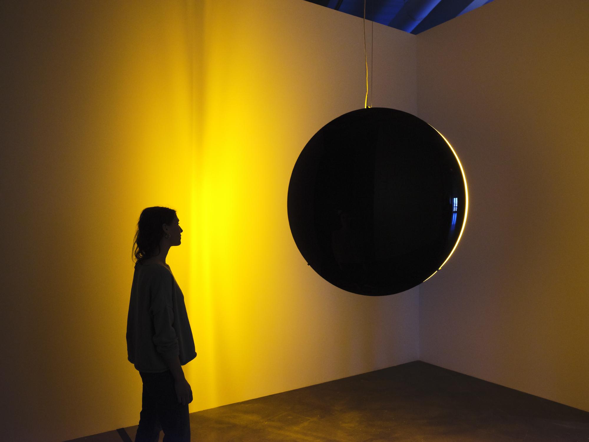 A shadowed figure observes a spherical black light sculpture emitting a soft golden hue