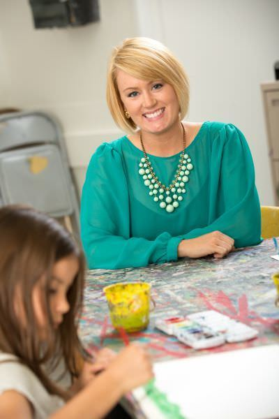 A person with blonde hair wearing a green dress shirt and statement necklace smiles while sitting at an art activity table with a child who is working on an art project