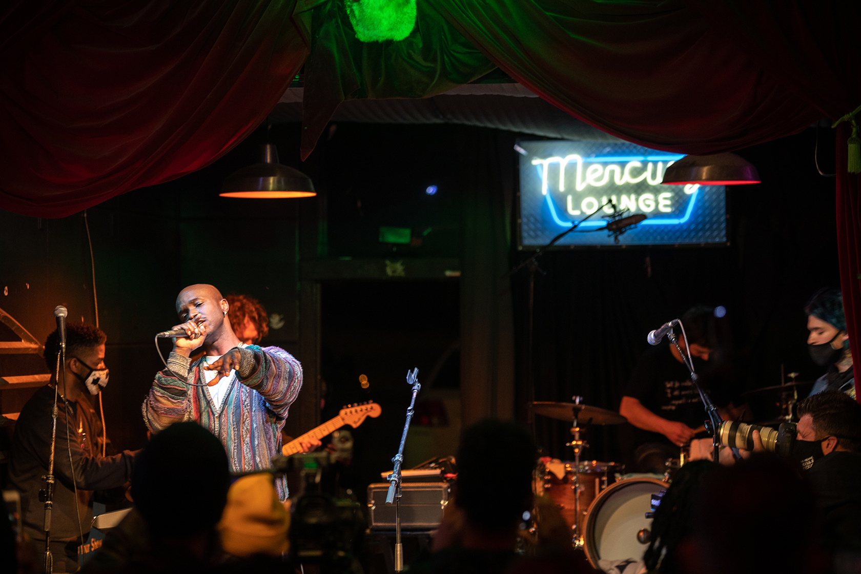 """A band (singer, guitarist, keyboardist, drummer) performs on a stage with the words """"Mercury Lounge"""" in neon behind them."""