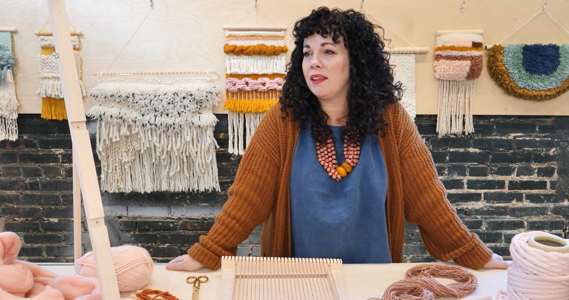 A figure with dark hair stands among fiber art and loom weaving materials