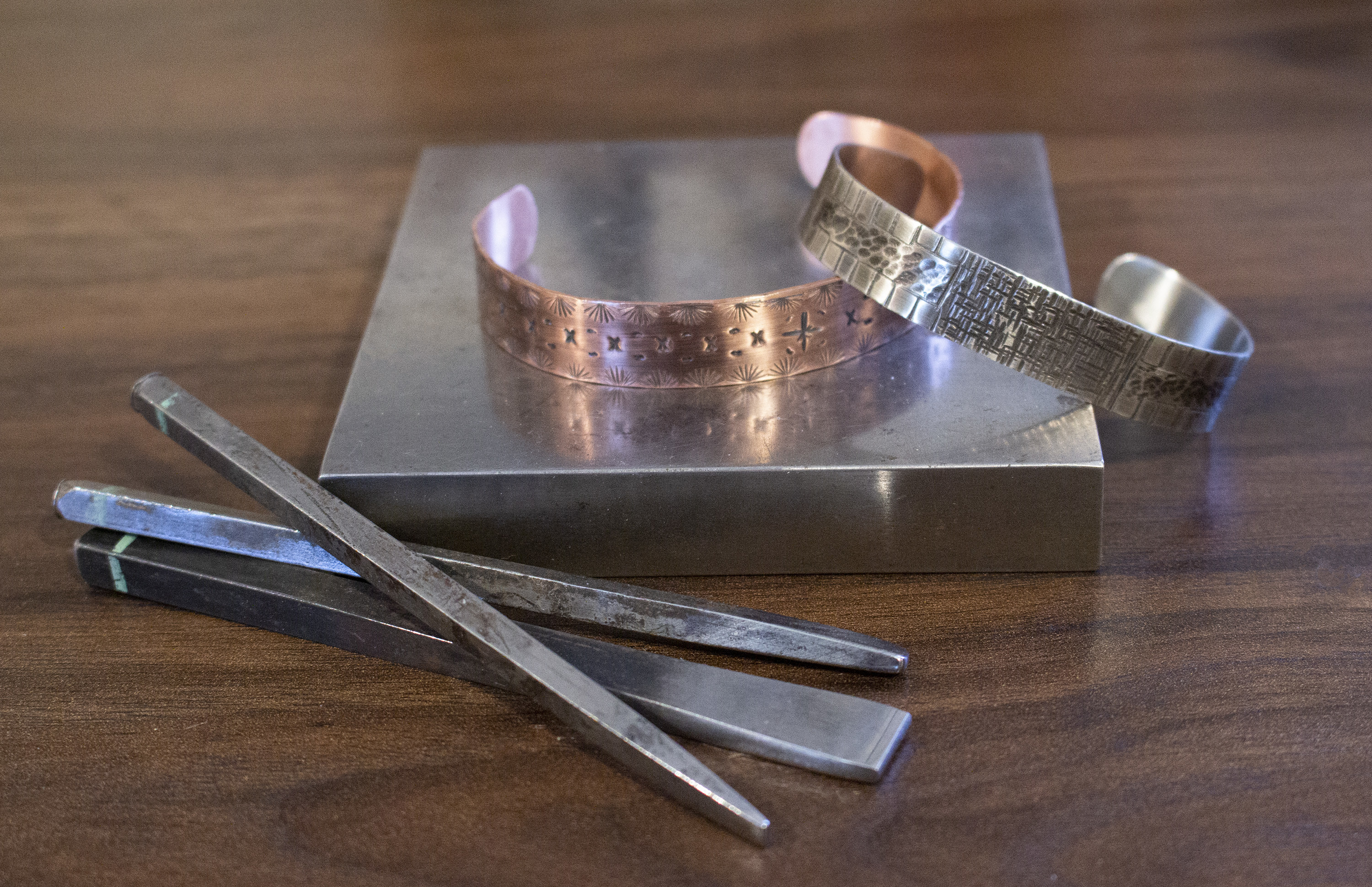 A set of decorated metal cuffs on a metal square with tools in foreground