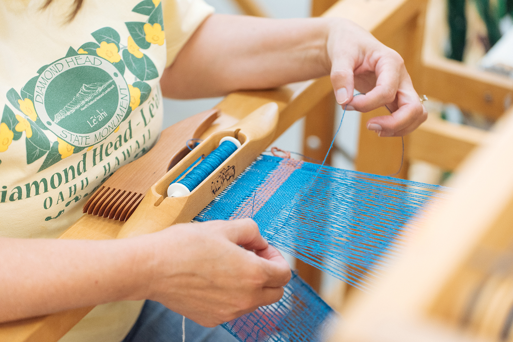 Hands operating a loom with blue and pink thread