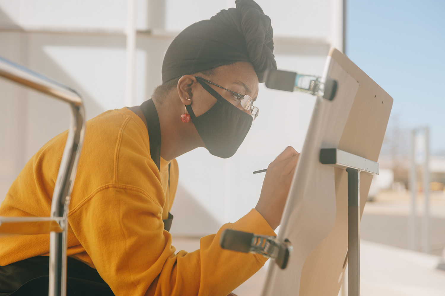 A person in a mustard-yellow sweatshirt, head wrap and mask draws on an easel outside