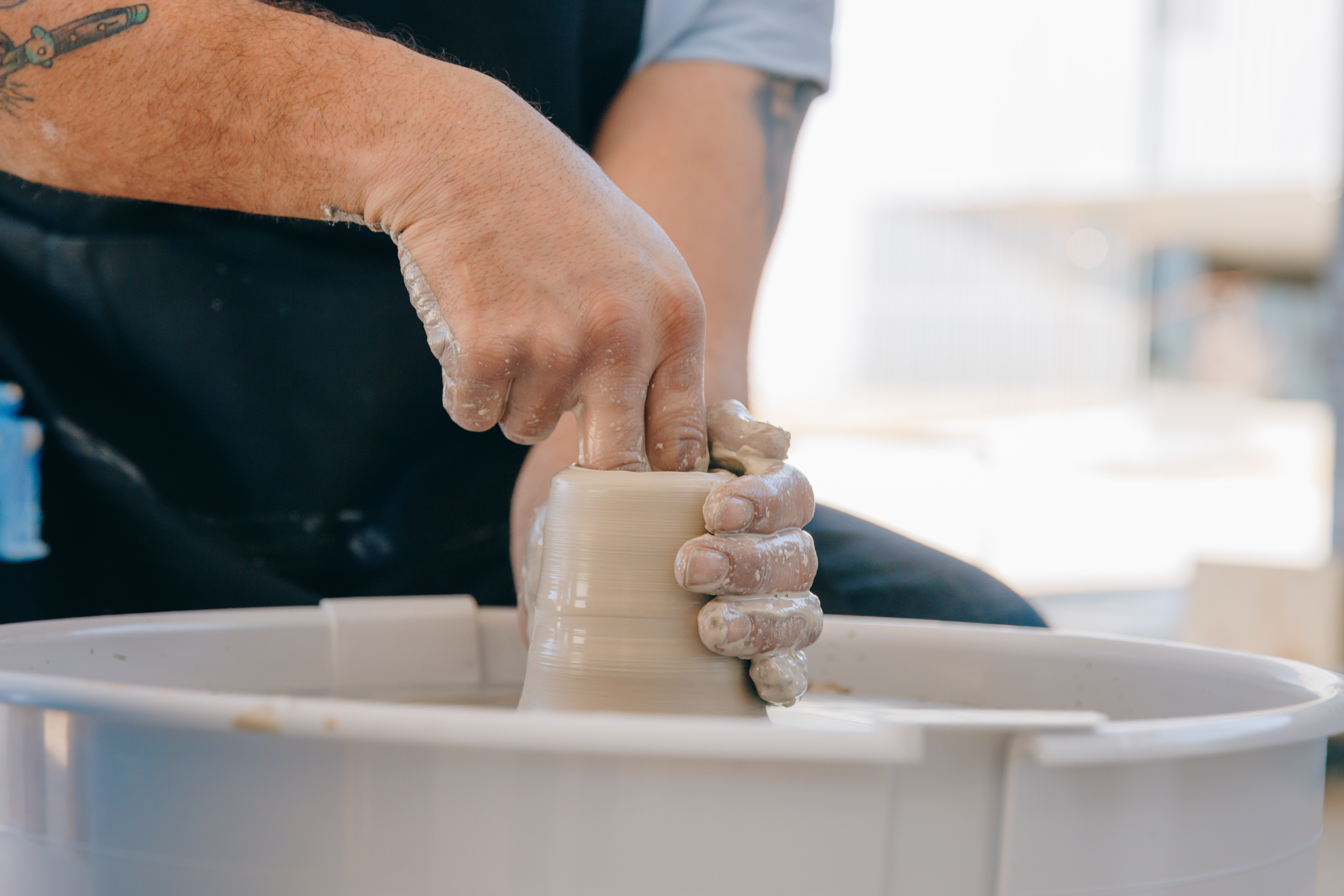Hands form a vessel on a pottery wheel