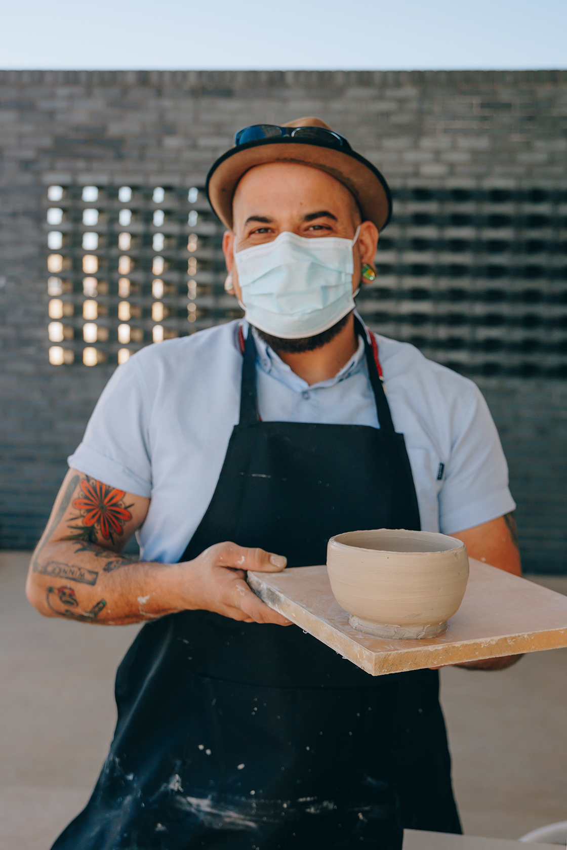A person in a mask and a studio apron holding ceramic bowl on tray with wall in background