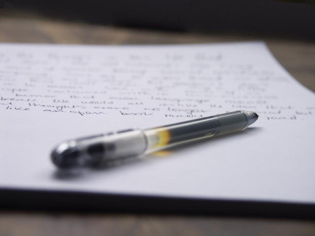 A pen lies on paper with writing out of focus