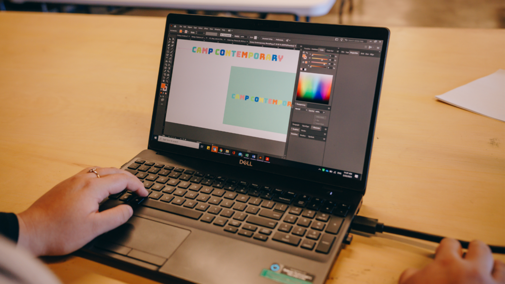A closely cropped image of a woman using Illustrator software on a laptop