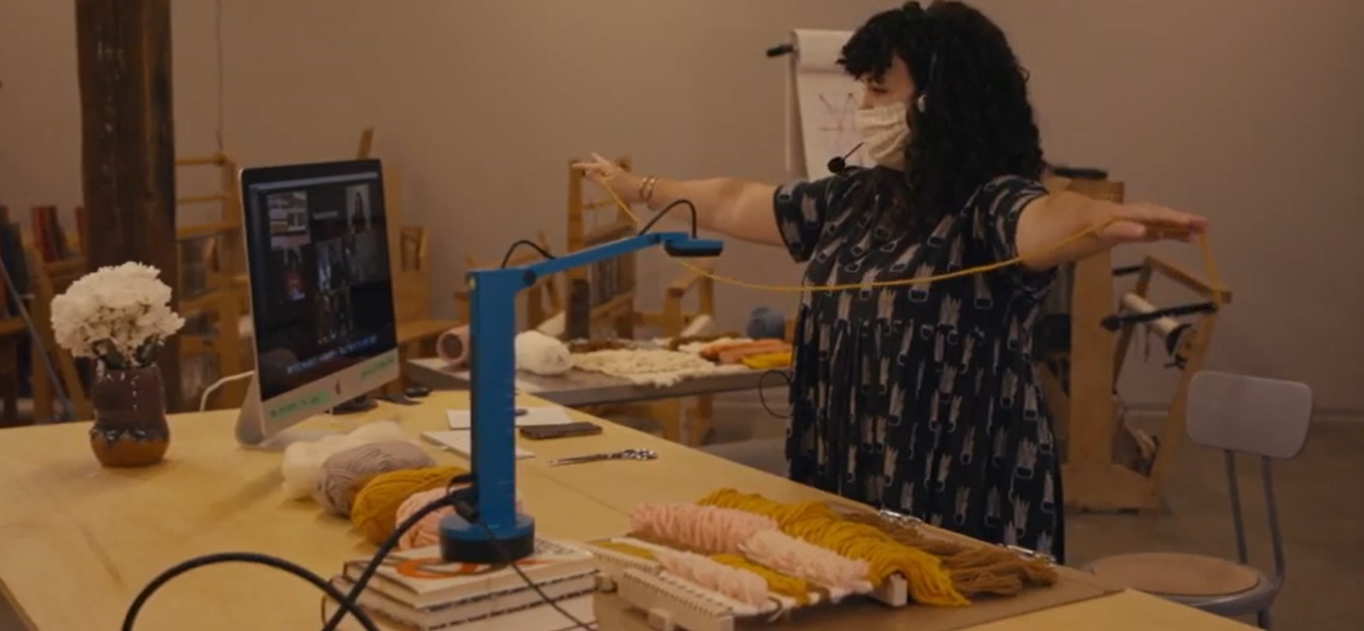A masked figure with dark hair and a blue shirt holds out a length of fiber in an online demonstration at a workstation