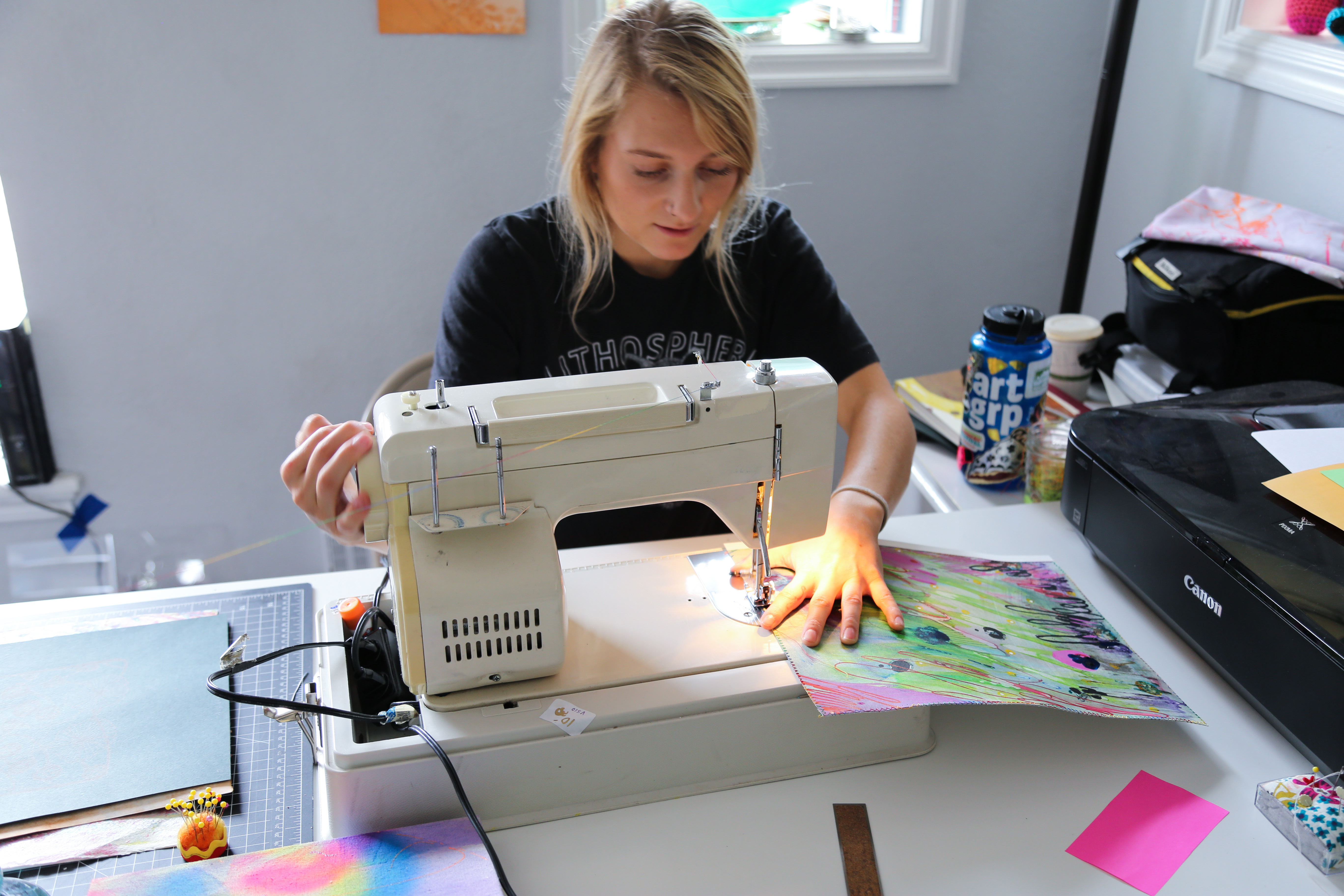 A person sits at a sewing machine, working on a colorful abstract panel