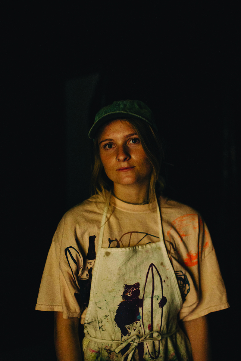 A figure wearing a paint-splattered apron looks into the camera