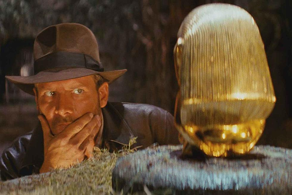 A still from the film Indiana Jones depicts the title character, wearing his trademark fedora, examining a golden object