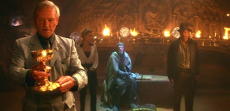 A figure examines a golden goblet in a still image from the film Indiana Jones and the Last Crusade