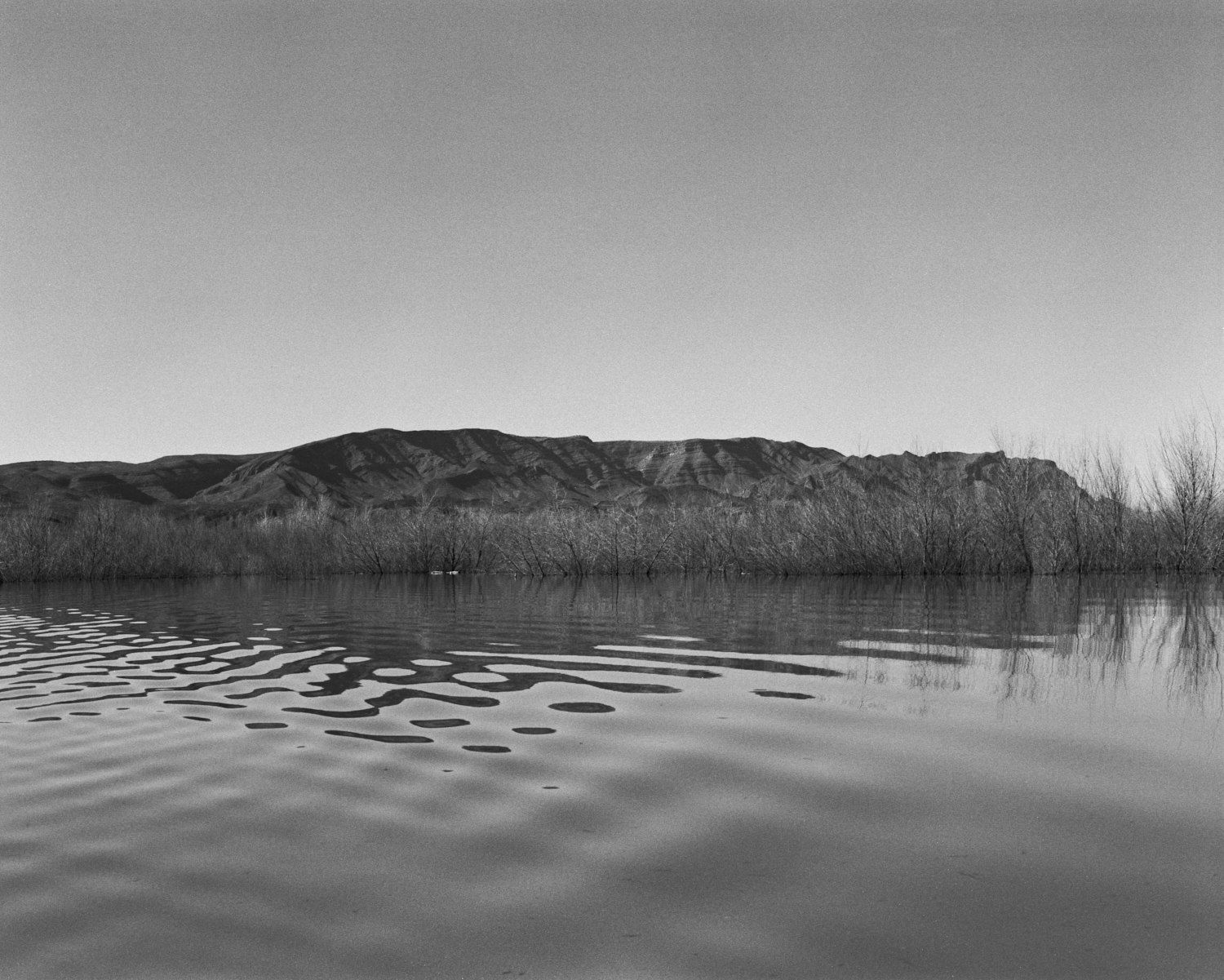 A black-and-white image of a butte surrounded by water
