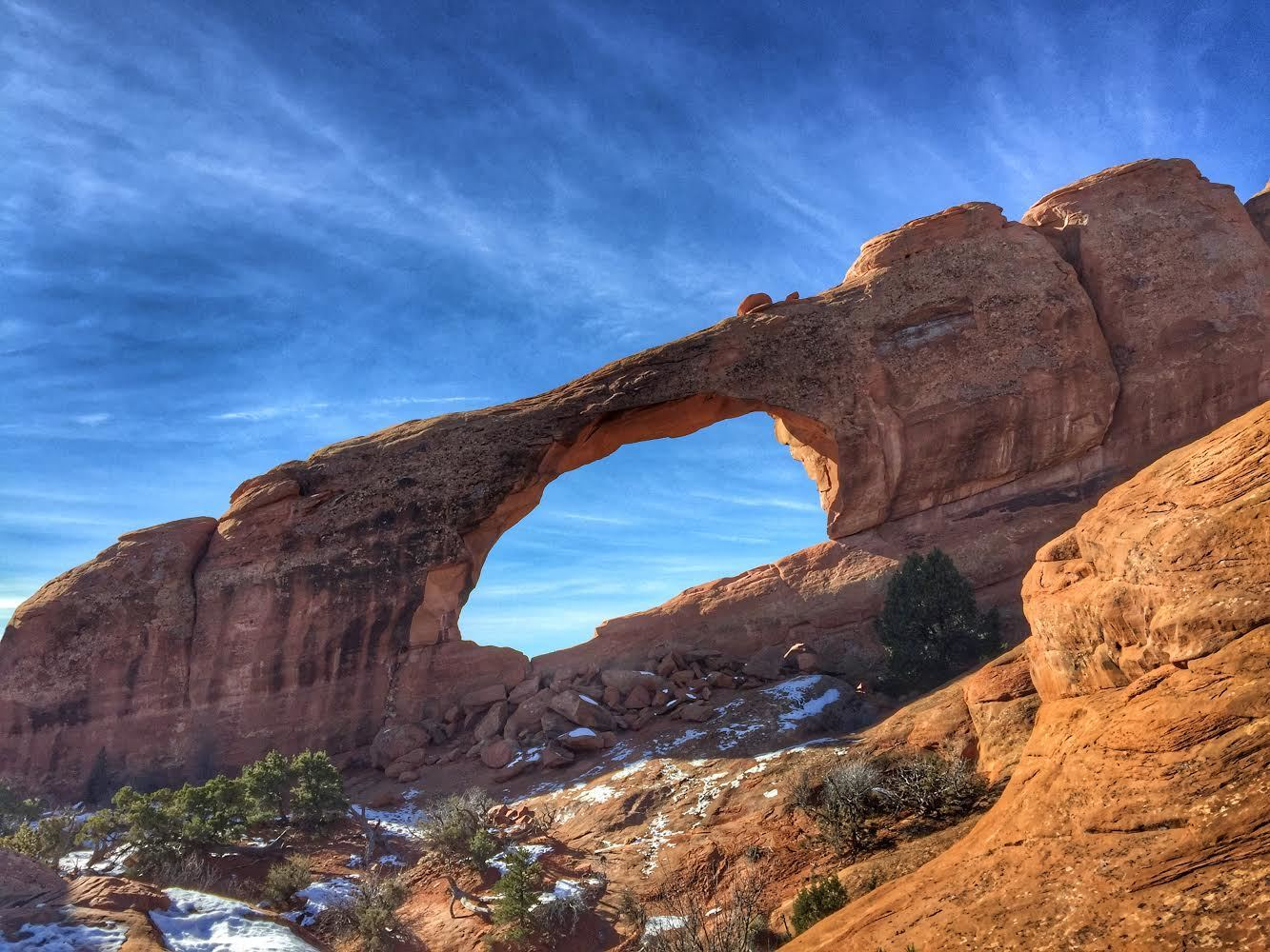A large boulder arch stretches across a blue sky, speckled with patches of snow