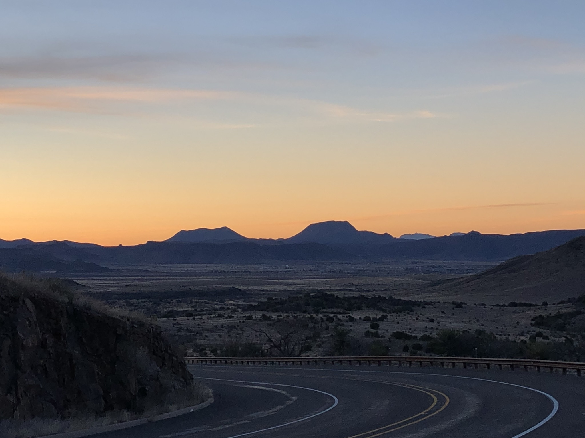 An evening scene in the desert of West Texas, featuring the silhouette of distant mesas beyond a curving lonely road