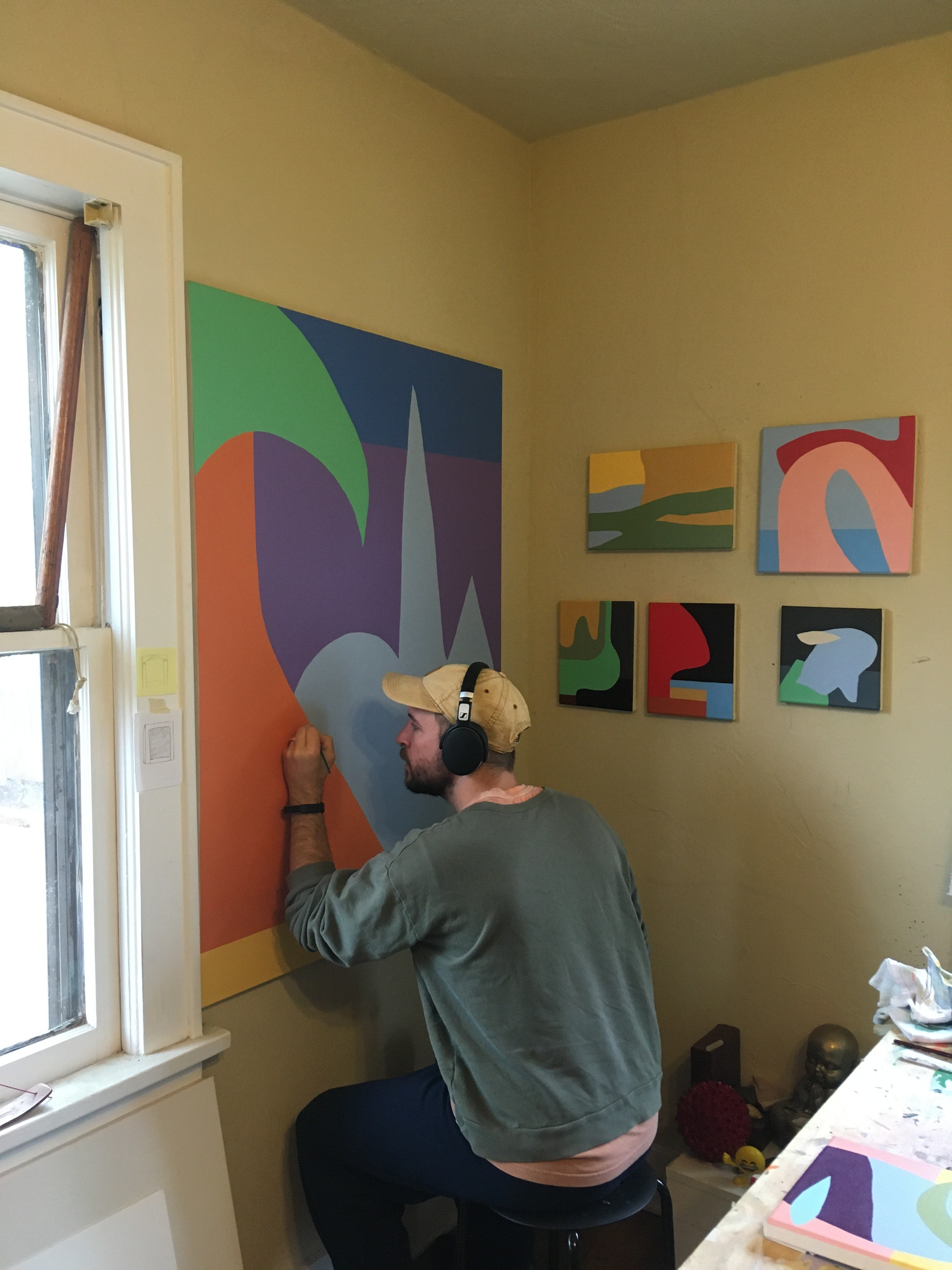 A figure wearing a baseball cap and headphones paints a large abstract landscape on a canvas in an art studio