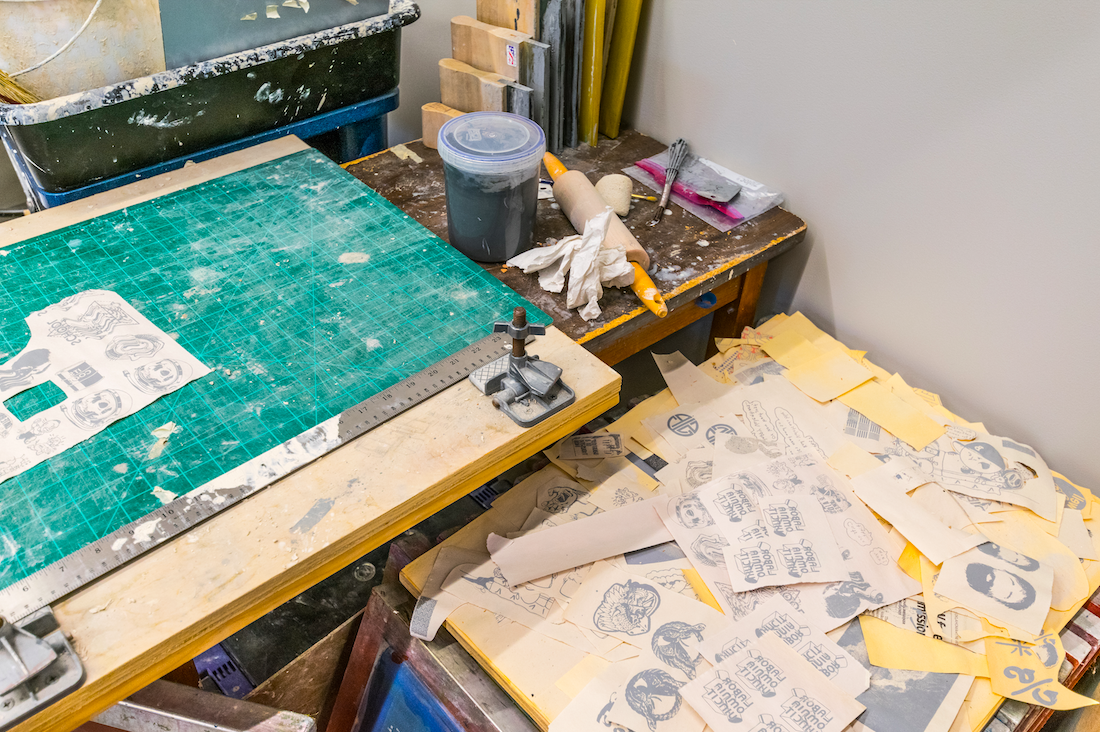A cluttered art studio featuring cut-out materials, rolling pins and other miscellaneous items for making art