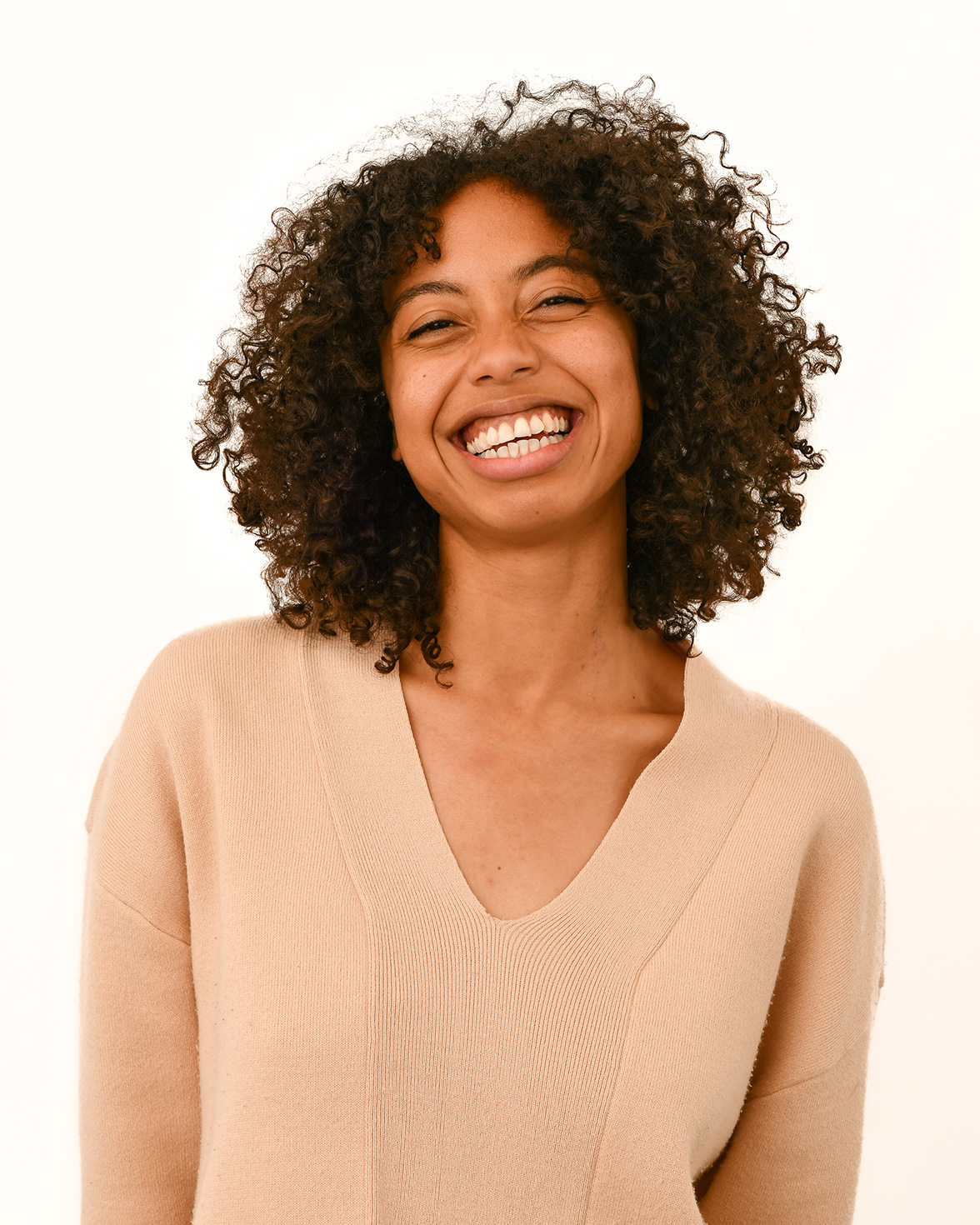 Smiling person with curly brown hair poses in a tan top