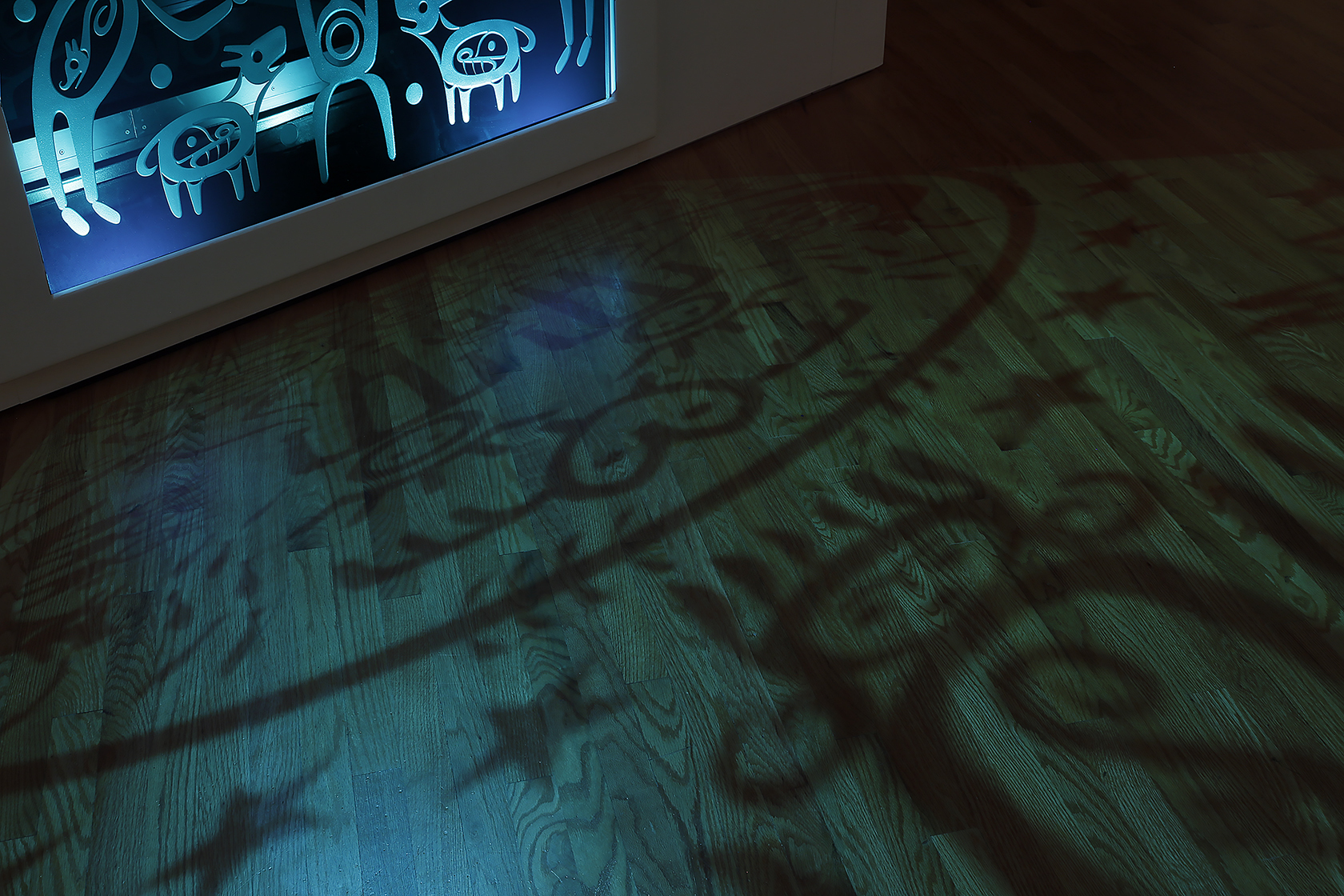 Shadows of stars, animals and figures are cast on from a sculpture onto a hardwood floor