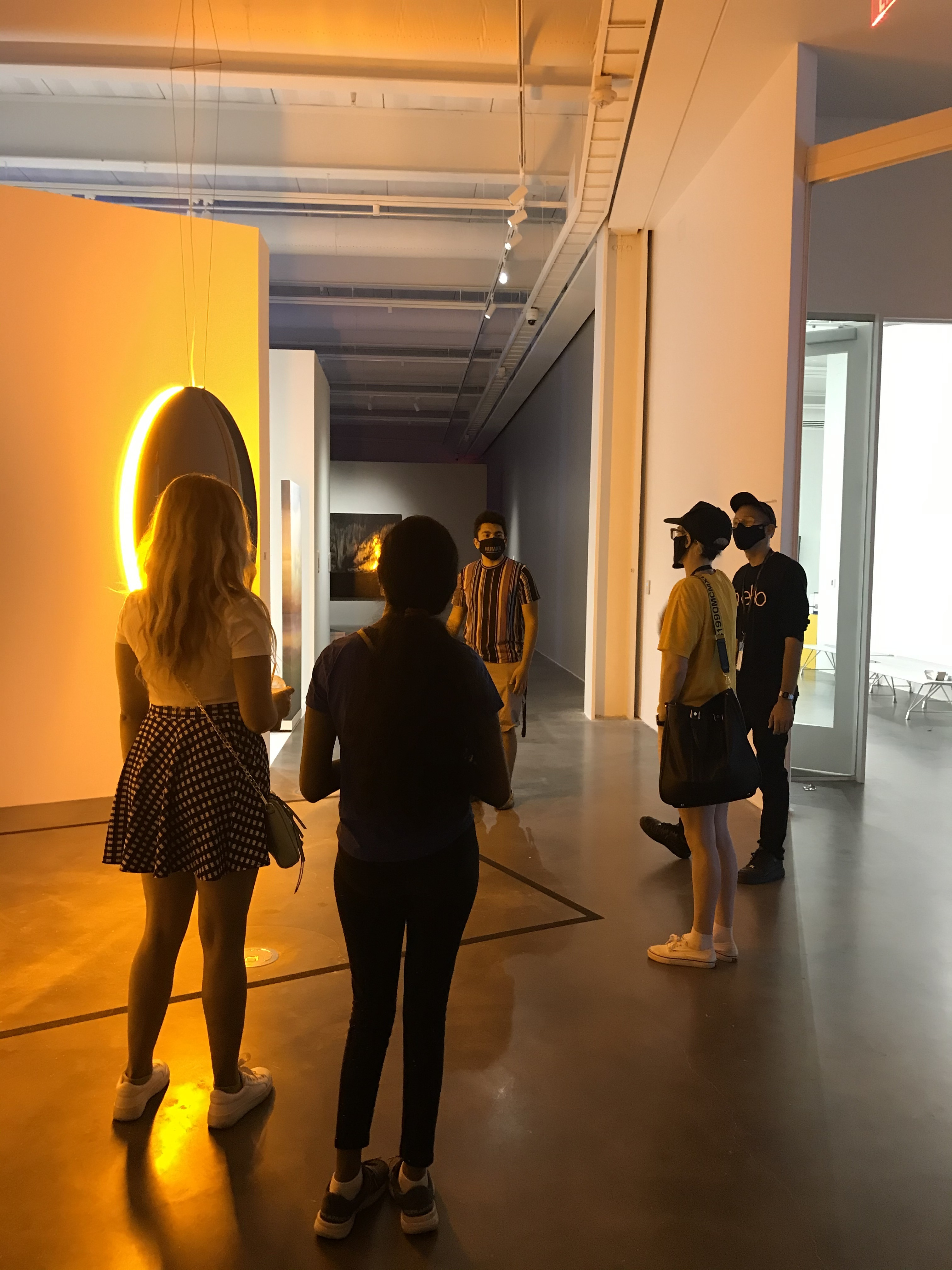 A group wearing face masks stand around a light sculpture casting the space in an orange glow