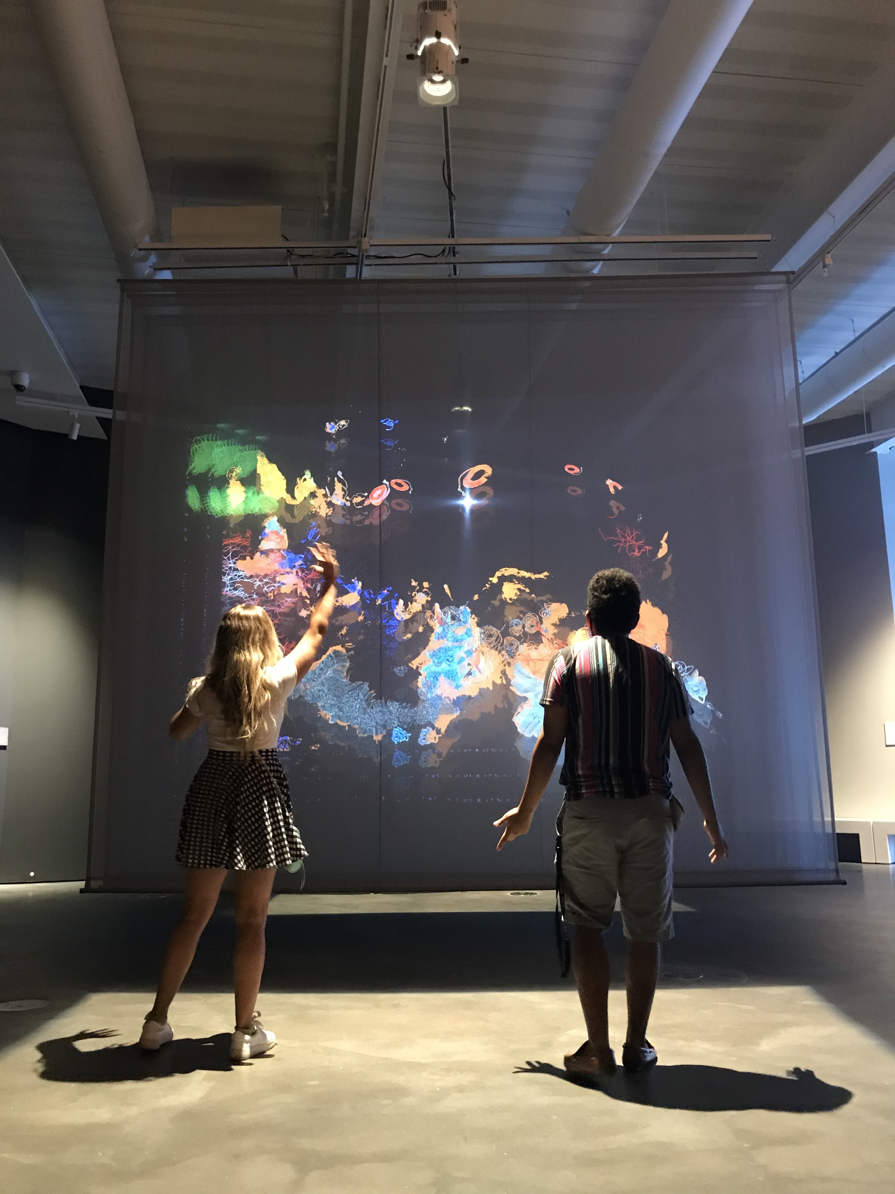 Two figures interact with a large screen displaying projected abstract art elements
