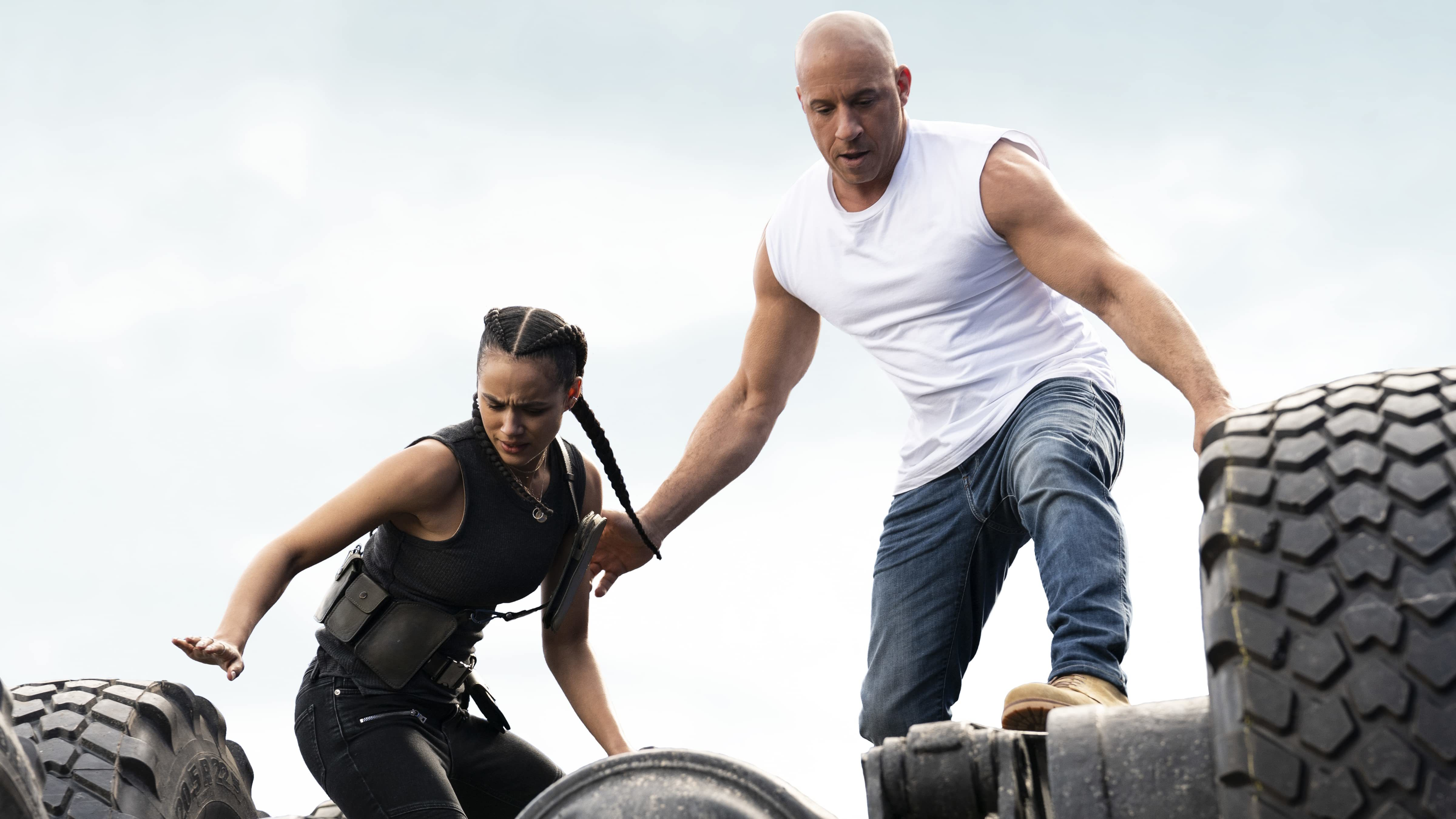 Two figures stand atop an overturned vehicle