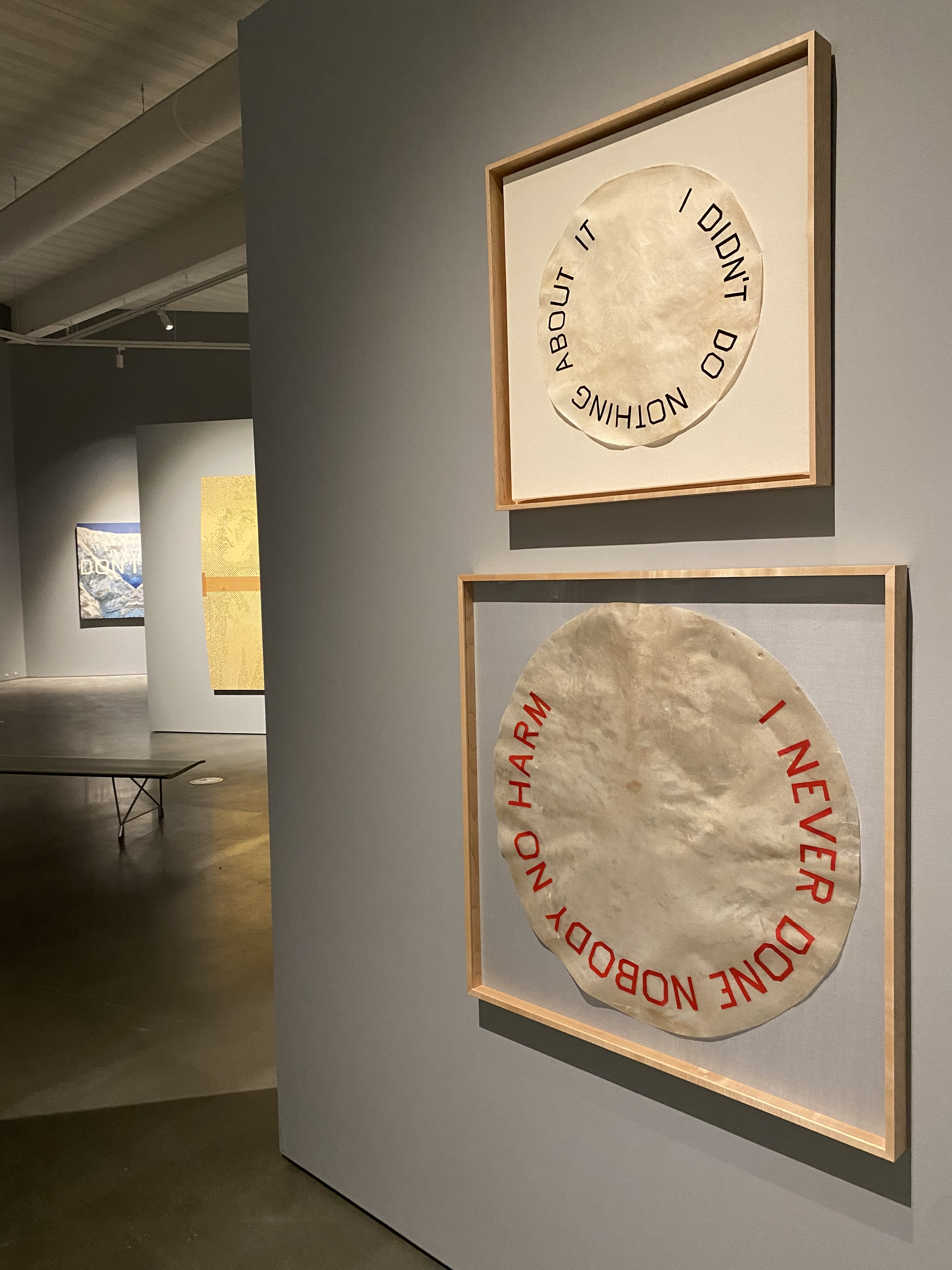 Two framed works of art depict drum skins with colloquial phrases imposed on them