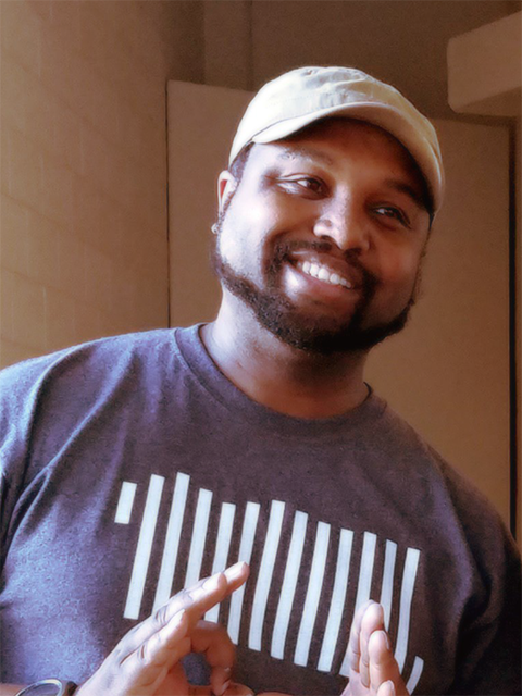 man with ballcap and beard holding hands in front of chest and smiling