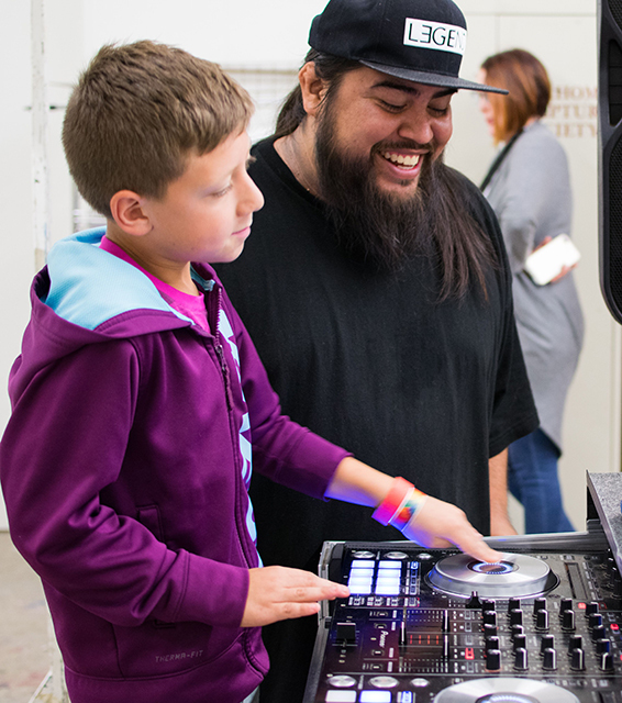 DJ instructs teenage boy on mixing techniques with woman in background out of focus