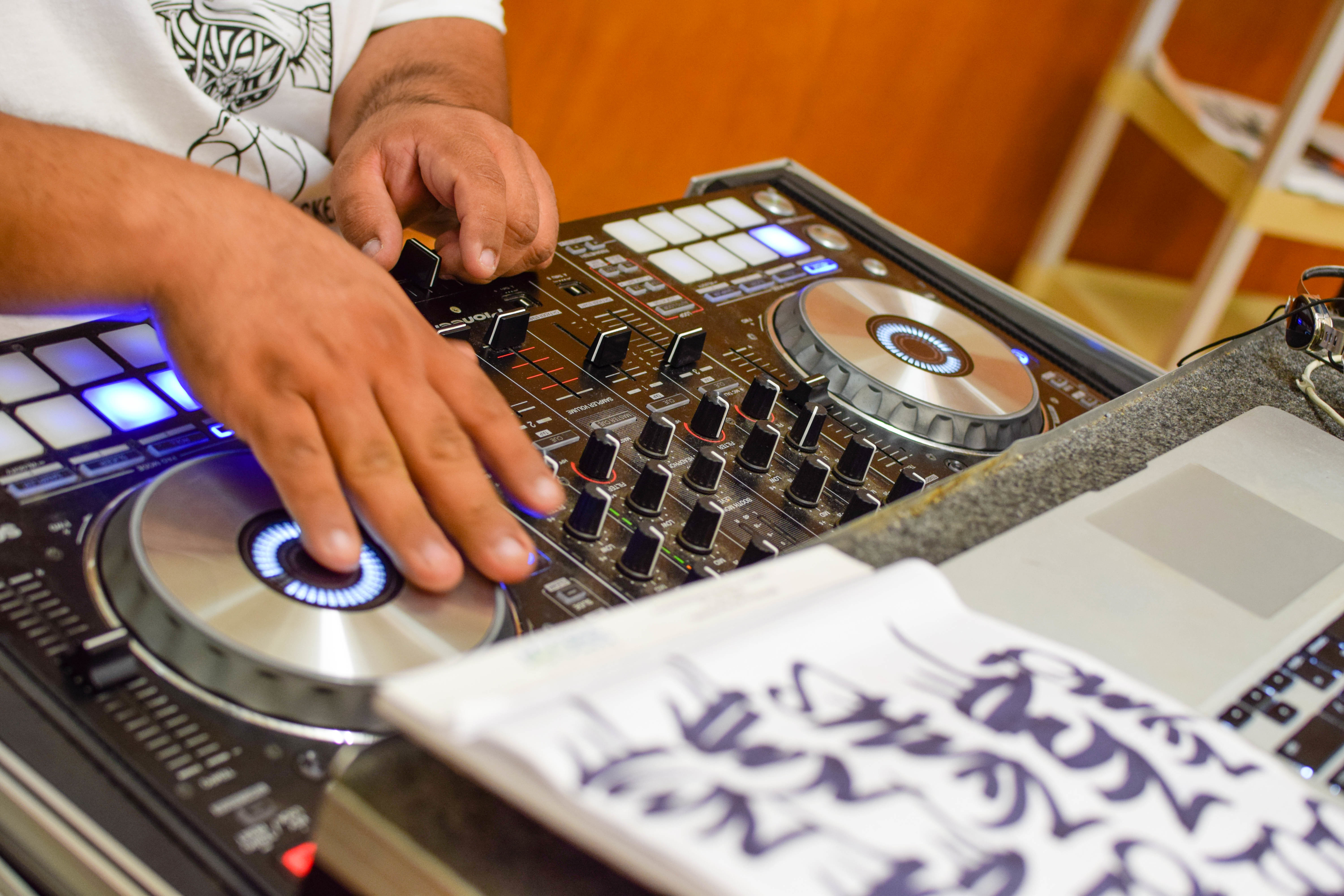 A pair of hands work a DJ turntable