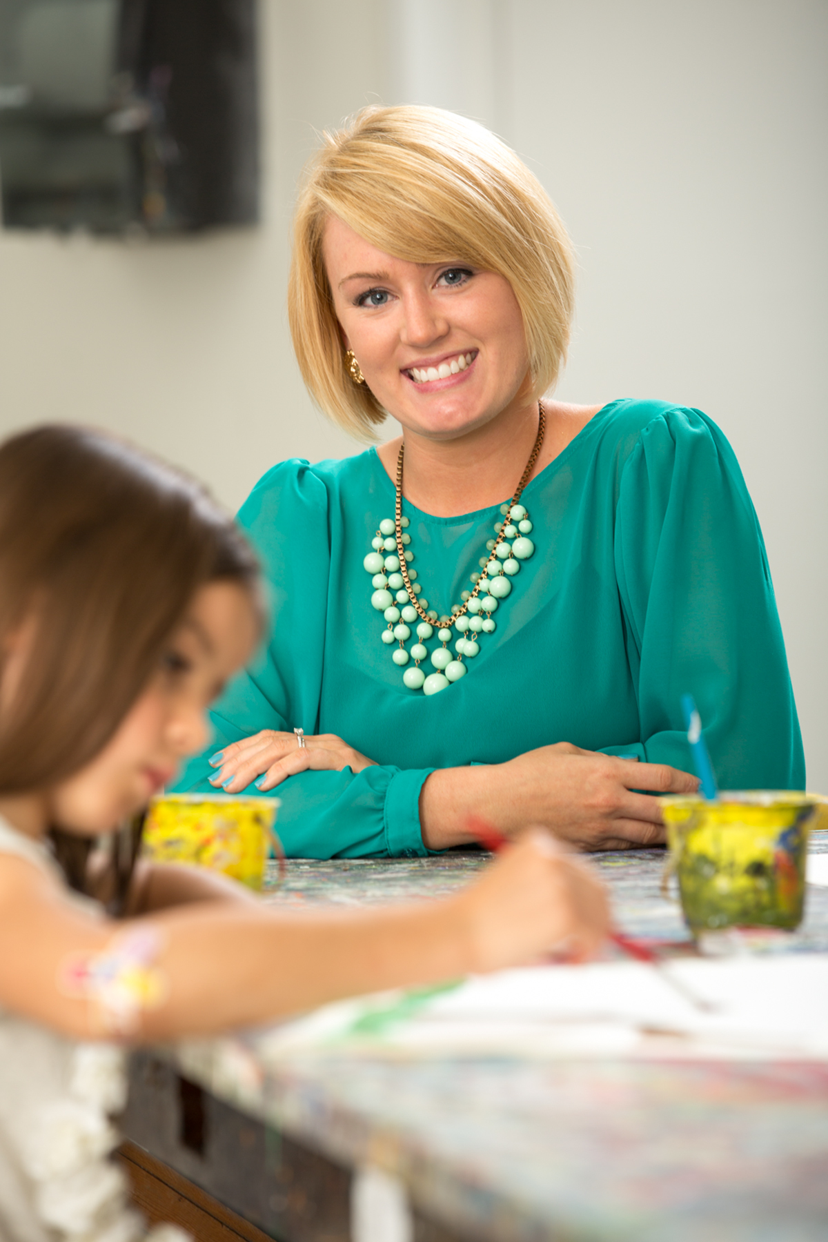 A blonde woman in an aqua-green shirt and statement necklaces smiles at a table while a child paints nearby