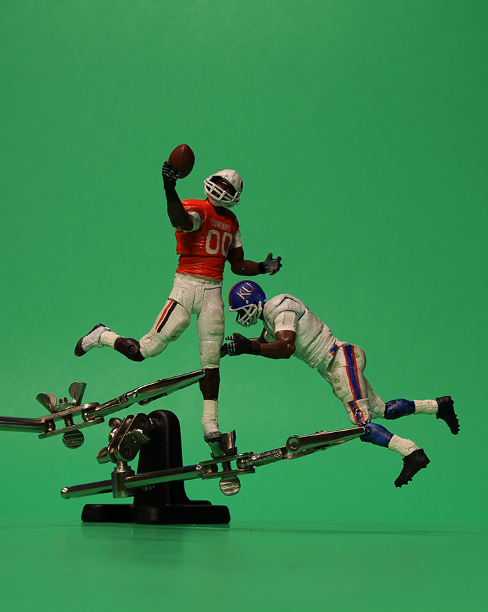 Two football action figures are held in place, mid-catch and tackle, by clamps on a green screen