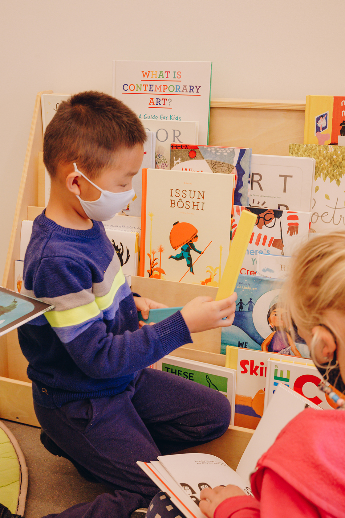 A child in a blue sweater and mask looks at books on a small shelf