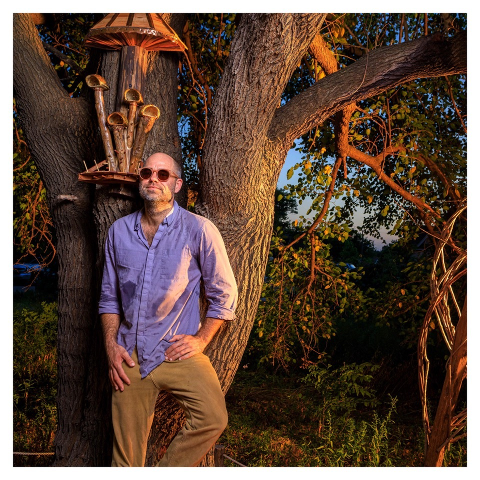 A person in sunglasses and a long-sleeved purple shirt poses in front of a tree adorned with ornate woodwork meant to resemble mushrooms