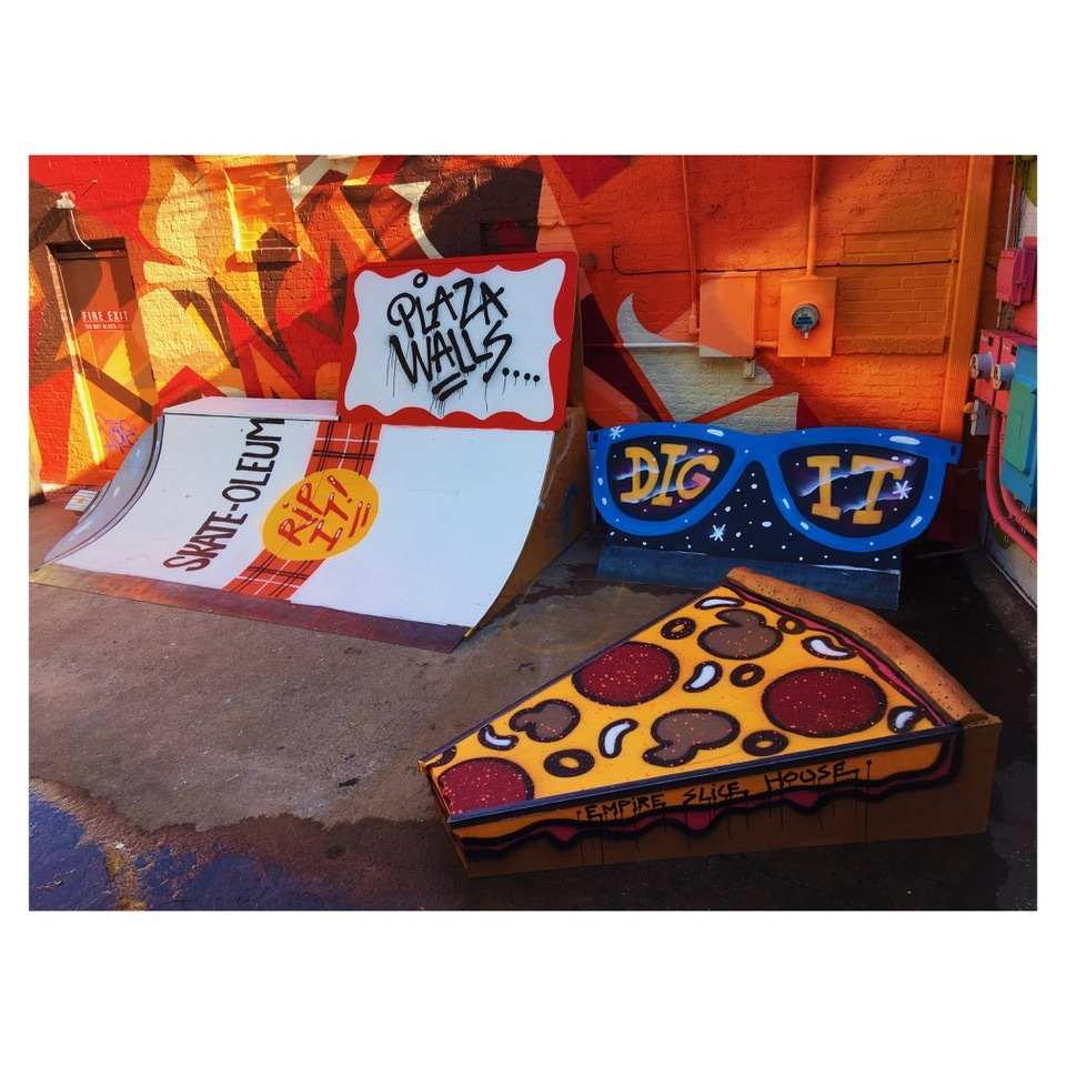 A whimsical public art installation featuring a large slice of pizza, sunglasses and a skateboard ramp
