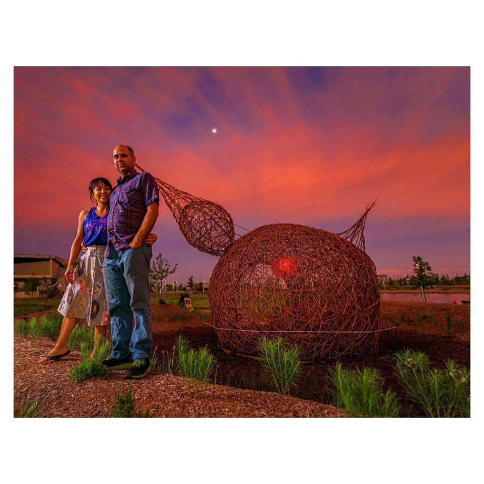 Two people pose in front of a woven willow sculpture in the shape of a bird as the sun sets behind them
