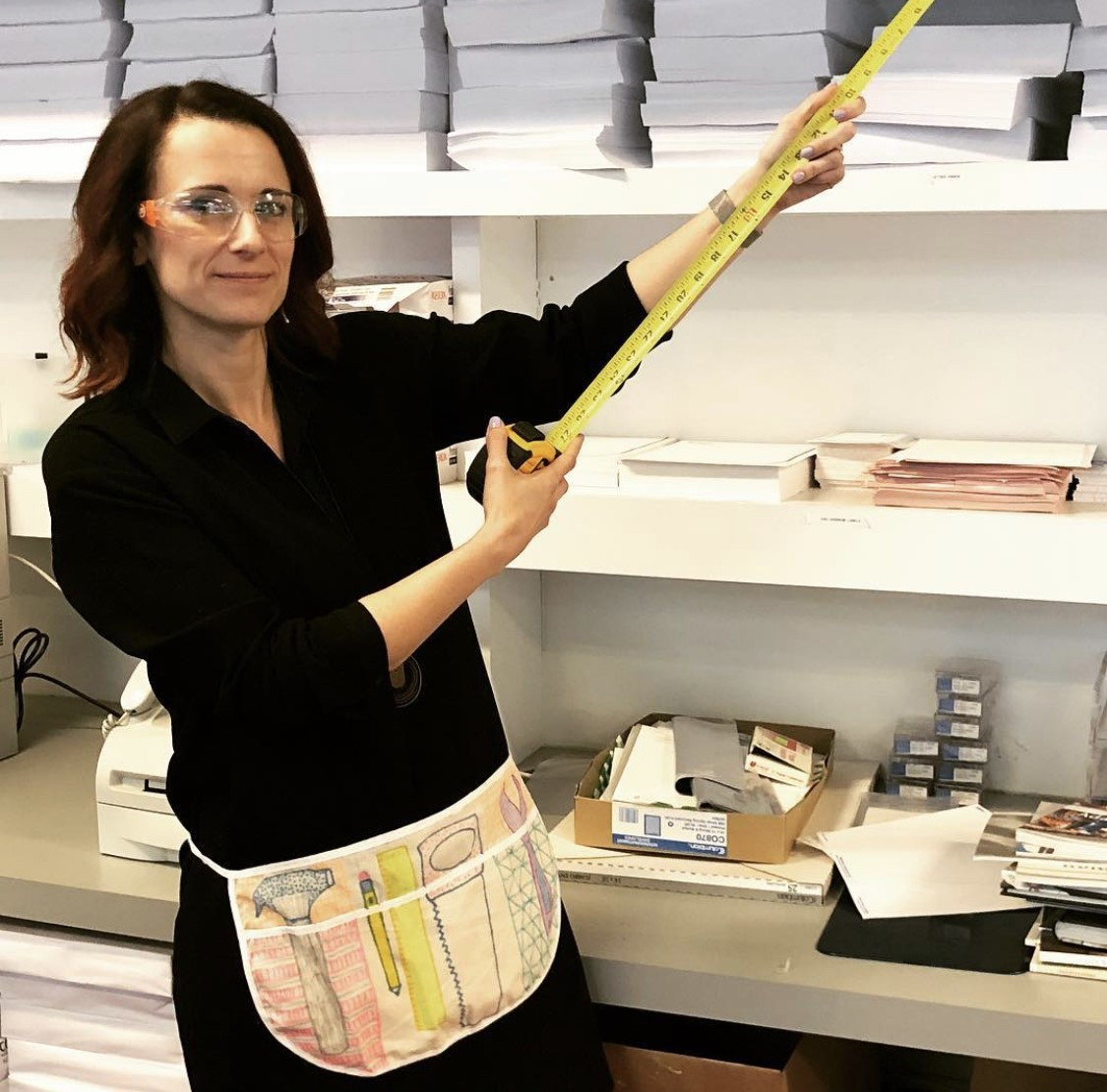A person wearing a drawn tool belt holds a tape measure