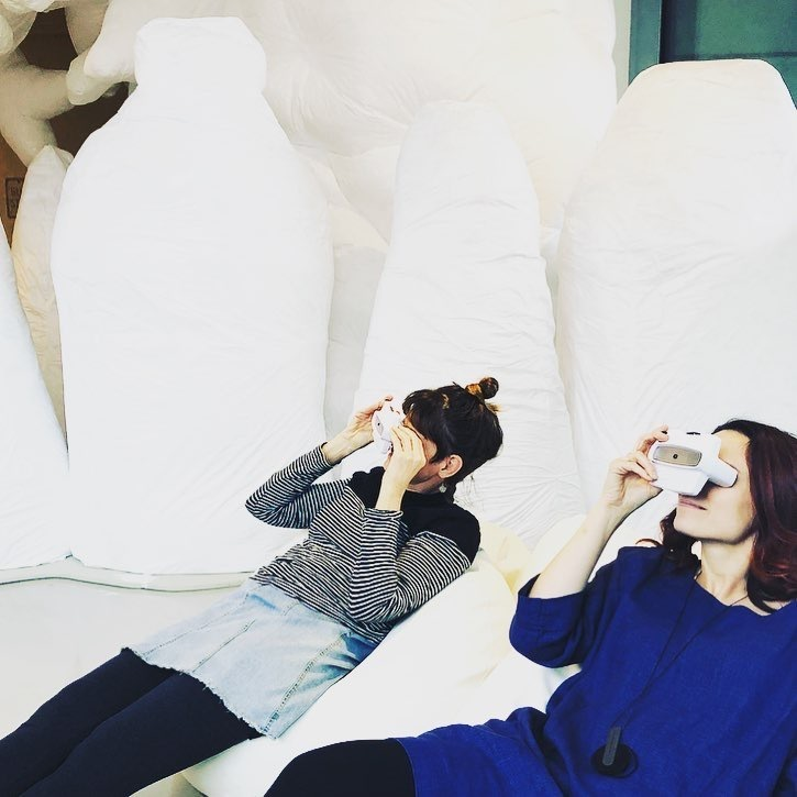 Two people lay on their backs, looking through viewfinders in an immersive art installation