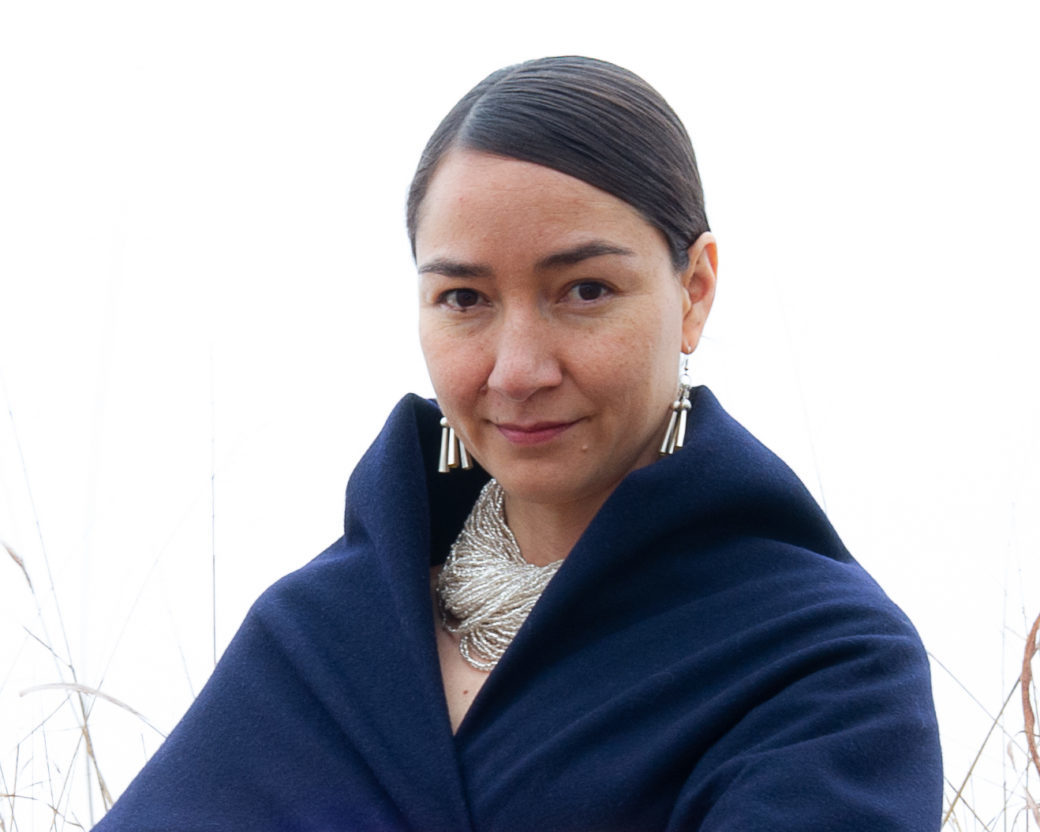 A person wearing Native American jewelry and a blue shawl smiles for the camera