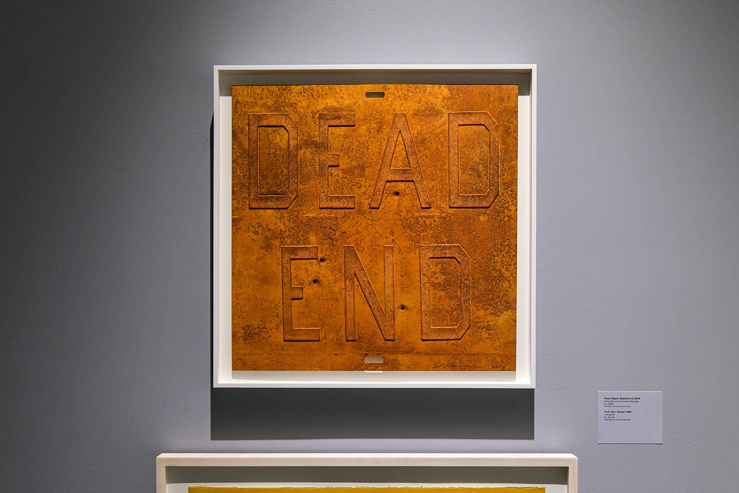 A framed art print on a gallery wall depicts the words DEAD END in a style resembling a rusted street sign