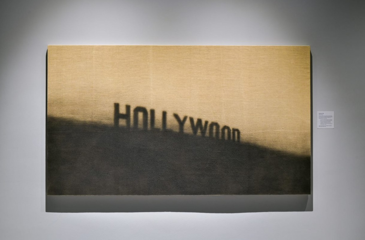A painting hanging on a gallery wall depicts the famed Hollywood sign in Los Angeles, with dark muted tones