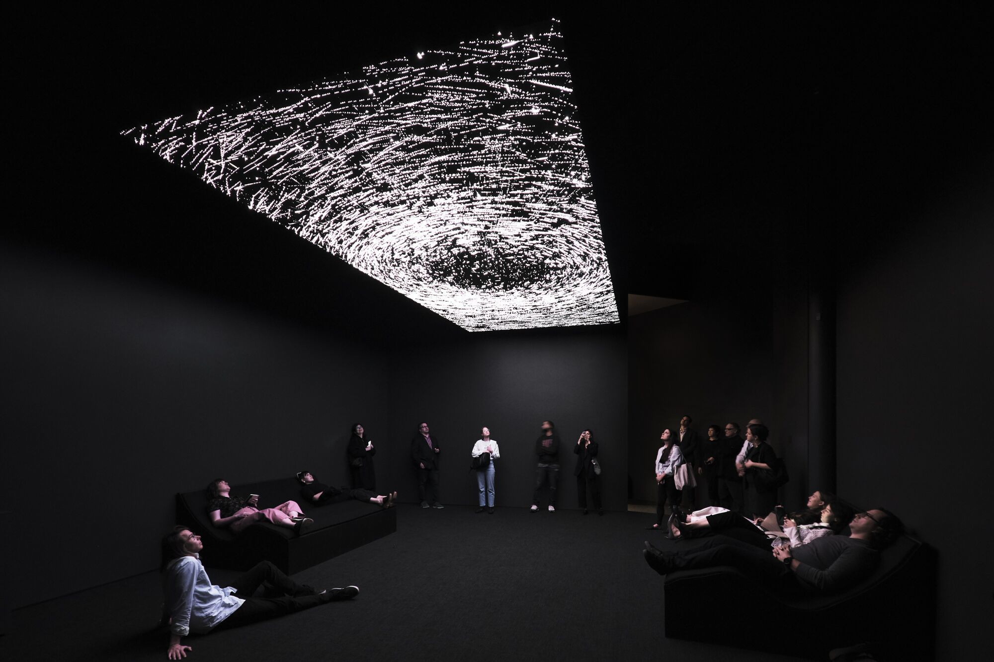 A roomful of people sit and stand beneath a light installation mimicking the stars of a night sky