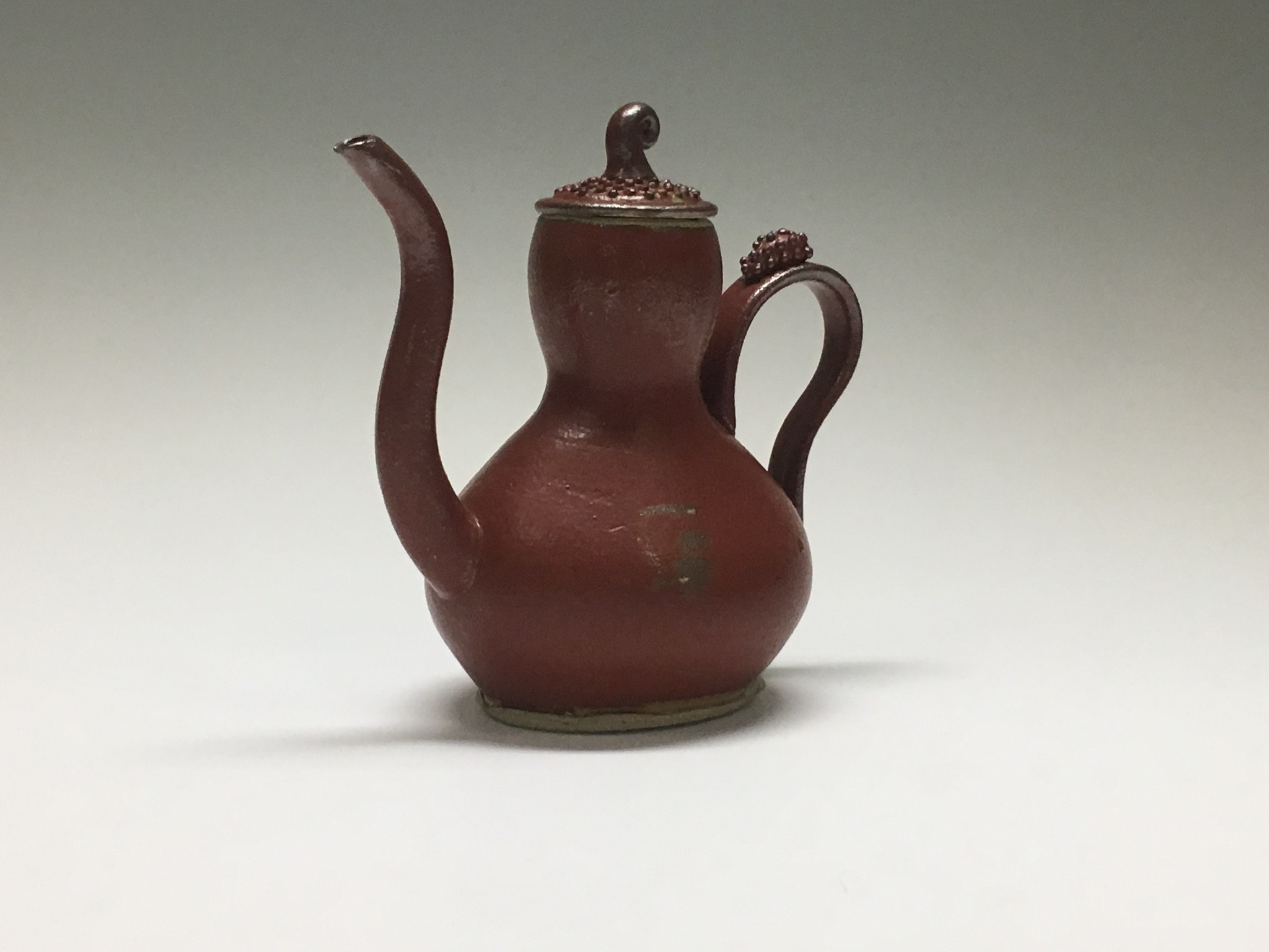 A photograph of a tall, red ceramic teapot