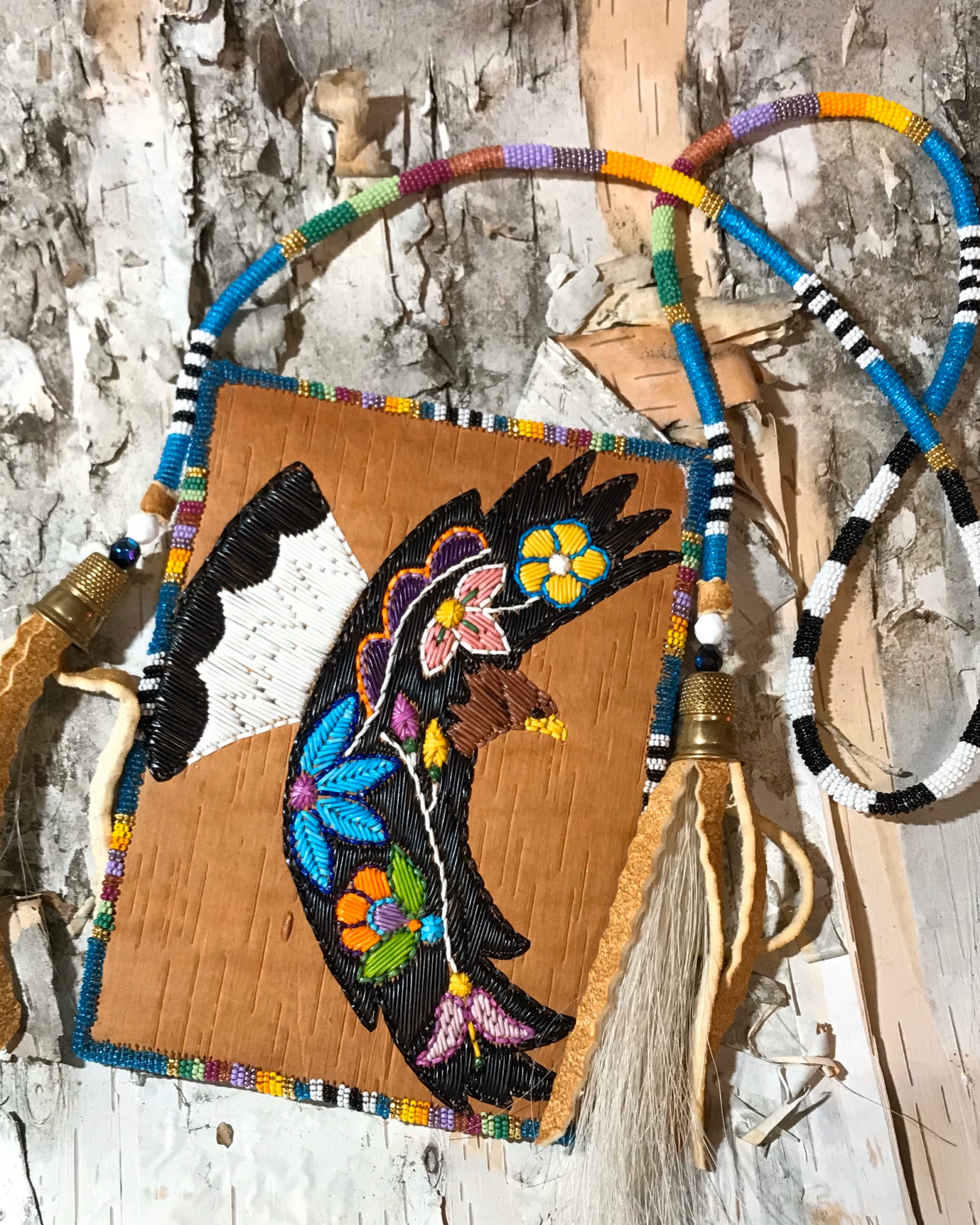 A piece of traditional woodland quillwork depicts colorful flowers against a slab of birch bark