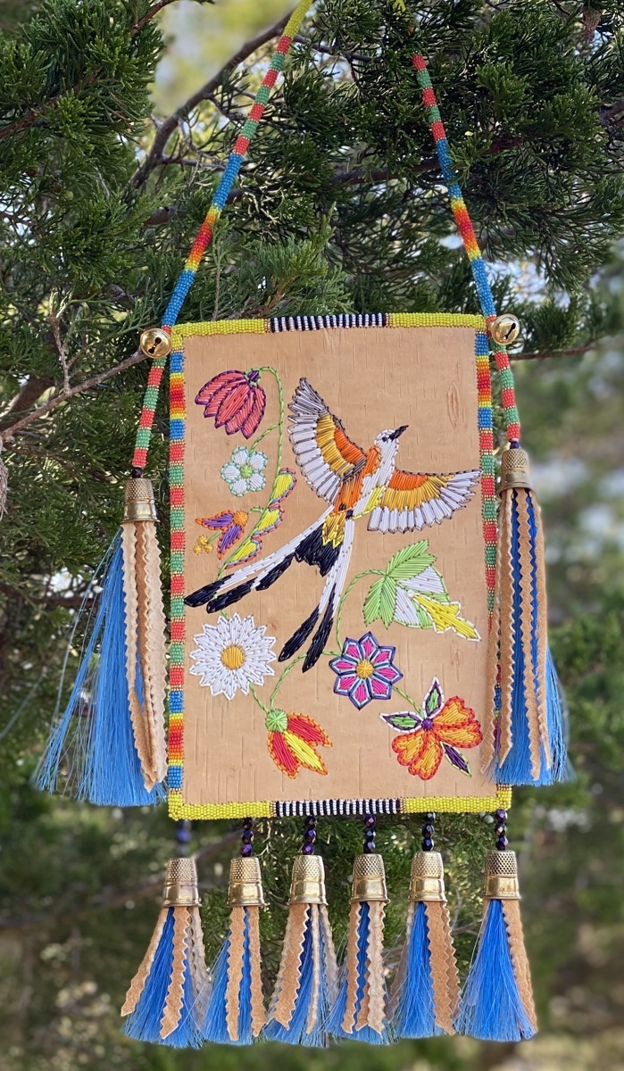 A hanging artwork features the depiction of a bird, along with tassles and vibrant colors