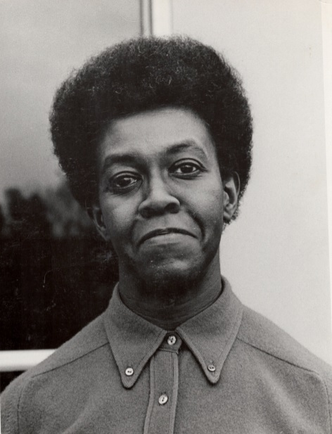 A tightly cropped black-and-white portrait of a person in a button-up shirt